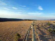 分裂在日出上面失去的水峡谷的栅栏在蒙大拿怀俄明边界的普莱尔山野马范围 库存图片