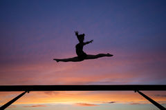 分裂在日落的平衡木跳跃 免版税图库摄影