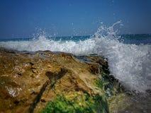 分裂挥动反对岩石在海 地中海挥动碰撞在岩石上 石头在有波浪的海在日落时间 库存照片