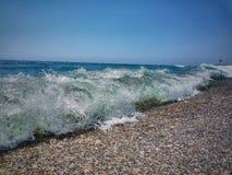 分裂挥动反对岸 地中海挥动碰撞在小卵石上 石头在有波浪的海在日落时间 免版税库存图片