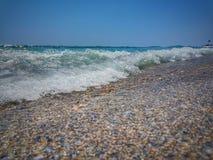 分裂挥动反对岸 地中海挥动碰撞在小卵石上 石头在有波浪的海在日落时间 库存图片