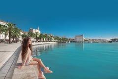 分裂,克罗地亚江边  有桃红色ba的年轻女性旅客 免版税图库摄影
