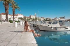 分裂,克罗地亚江边  有桃红色ba的年轻女性旅客 图库摄影