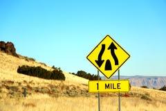 分道公路从杂草和岩石开始在路线66的sgin在内华达州,作为背景 库存图片
