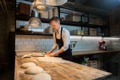 分配与长凳切削刀的贝克面团在面包店 免版税图库摄影