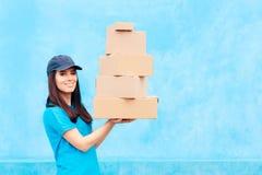 分配服务拿着许多纸板包裹的交付工作者 库存图片