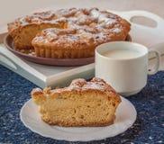 分配蛋糕用凝乳和一个杯子牛奶 库存照片