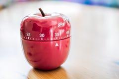 35分钟-厨房在苹果计算机形状的蛋定时器在木表上 库存照片