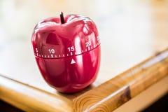 15分钟-厨房在苹果计算机形状的蛋定时器在木表上 免版税库存照片