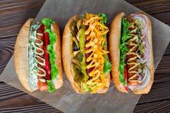 分类三个热狗用番茄酱、芥末和沙拉在木背景 免版税图库摄影