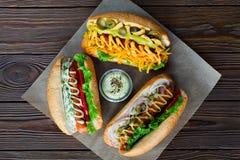 分类三个热狗用调味汁和沙拉在木背景 免版税库存照片