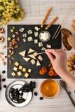 分类用乳酪、果子和坚果在黑石头用妇女手 免版税库存照片