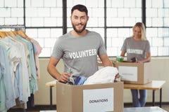 分离衣裳的微笑的志愿者画象从捐赠箱子 免版税库存照片