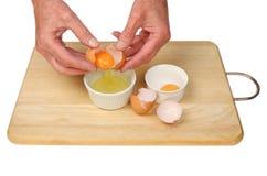 分离鸡蛋的手 图库摄影