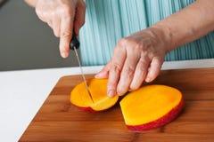 切一个新鲜的芒果的女性的手 免版税库存图片