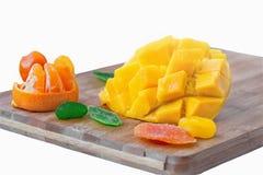 切一半芒果用橘子、糖煮的说谎在一个木板的金桔和其他果子隔绝在白色背景 库存图片
