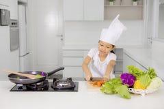 切一棵红萝卜的小女孩在厨房里 库存图片