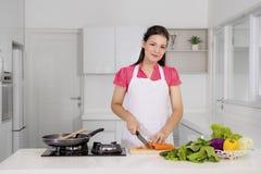 切一棵红萝卜的愉快的妇女在厨房里 免版税图库摄影