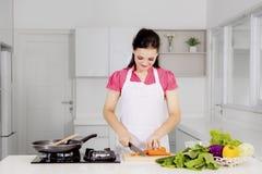 切一棵红萝卜的美丽的妇女在厨房里 免版税图库摄影