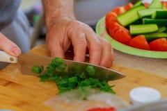 切与一把厨刀的葱在一个木切板 在切板的新鲜的葱 免版税库存照片