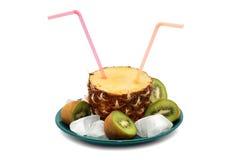 切与两支桃红色管的菠萝在一块绿色板材,围拢由猕猴桃切成两半和冰块 库存图片