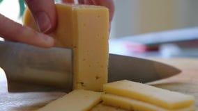 切与刀子的一位中间年迈的厨师的宏指令乳酪在木板,关闭 影视素材
