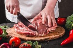 切与刀子的厨师屠户猪肉在厨房,烹调食物 库存照片