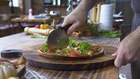 切与刀子的厨师的手比萨在木桌,食物背景上 切在餐馆的过程的关闭热的比萨 股票视频