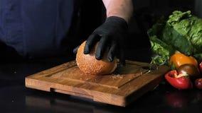 切与芝麻籽的小圆面包与在木板的一把厨刀,隔绝在黑背景 股票录像