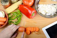 切与菜和数字式片剂的人一棵红萝卜 库存照片