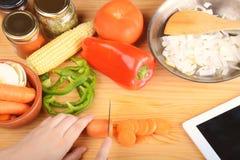切与菜和数字式片剂的人一棵红萝卜 库存图片