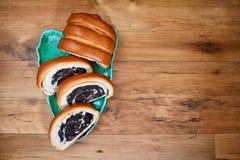 切了与说谎在绿松石板材的罂粟种子的红润新鲜的小圆面包以木表面上的一片叶子的形式,copyspace 免版税图库摄影