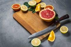 切从桔子,葡萄柚,柠檬,在切板的石灰切片 库存图片