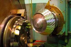 切削刀调控金属,并且油从冷却和润滑的日志流动 金属工艺产业通过切开,齿轮 免版税库存图片