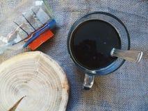 切口树匾、小船和一个杯子无奶咖啡 免版税图库摄影