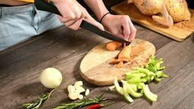 切在一个木切板的女性厨师手特写镜头被剥皮的红萝卜在被切的菜旁边 ??  股票视频