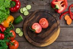切在一个木板和菜的蕃茄在桌上 库存照片