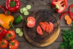 切在一个木板和菜的蕃茄在桌上 免版税库存图片