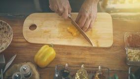 切在一个烹调委员会的男性手黄色辣椒粉 库存图片