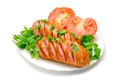切在一块板材油煎的香肠用蕃茄和荷兰芹在白色背景 库存图片