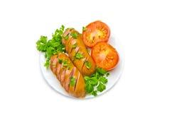 切在一块板材油煎的香肠用蕃茄和荷兰芹在白色背景 免版税库存图片
