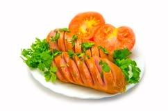 切在一块板材油煎的香肠用蕃茄和荷兰芹在白色背景 免版税图库摄影