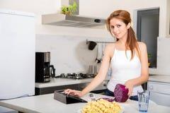 切在厨房观看的片剂个人计算机的红头发人女孩 免版税库存图片