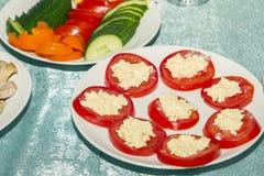 切在圈子蕃茄用酸奶干酪或乳酪在白色板材 在自助餐桌上的冷的快餐 侧视图和拷贝空间 免版税库存照片