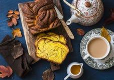 切在土气木砧板、奶茶和一个茶壶的南瓜奶油蛋卷桂香在蓝色背景,顶视图 库存图片