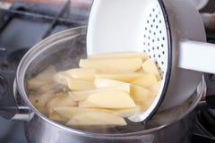 切在平底深锅的土豆有开始的水煮沸 库存照片