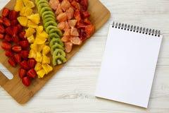 切好的新鲜的未加工的果子在切板和笔记本安排了在白色木桌,顶视图上 从上,平的位置, 库存图片