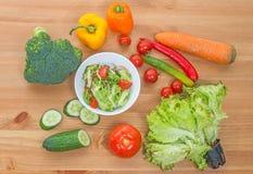 切好的沙拉和整个新鲜蔬菜在木桌上 顶视图 库存图片