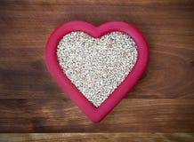 切好的燕麦在红色心脏 免版税库存照片
