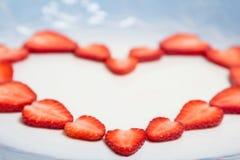 从切好的红色水多的草莓的美好的心脏标志 库存照片